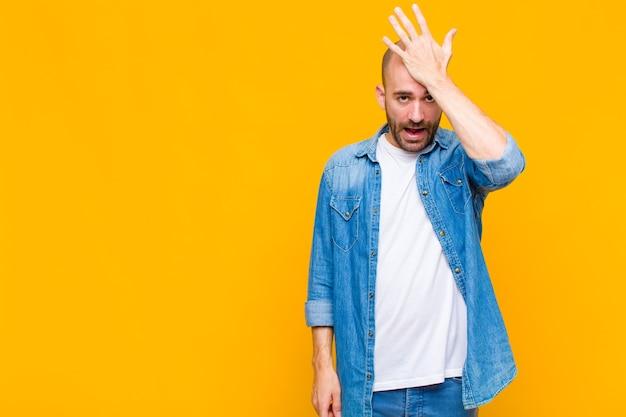 Hombre calvo levantando la palma de la mano hacia la frente pensando ¡uy, después de cometer un error estúpido o recordar, sentirse tonto!