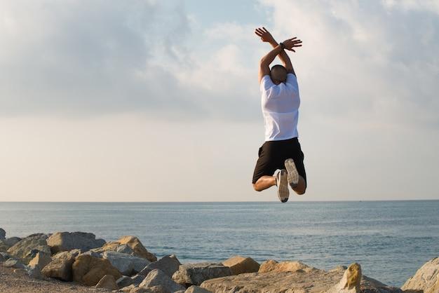 Hombre calvo libre que salta y que agita las manos