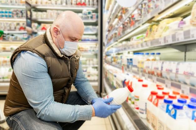 Un hombre calvo con una máscara médica elige productos lácteos en un supermercado. nutrición adecuada y un estilo de vida saludable. autoaislamiento durante la pandemia de coronavirus. de cerca.