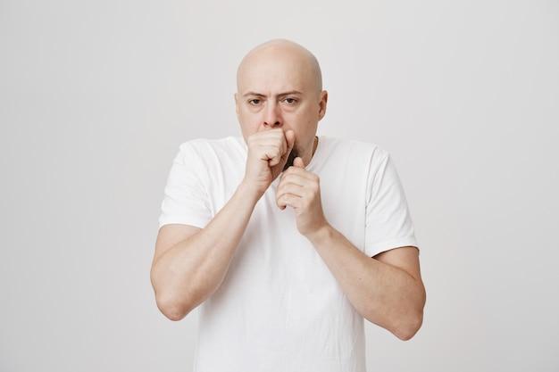 Hombre calvo de mediana edad tosiendo en el puño
