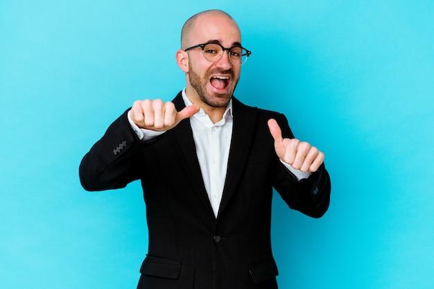 Hombre calvo de negocios joven aislado en la pared azul levantando ambos pulgares, sonriente y confiado