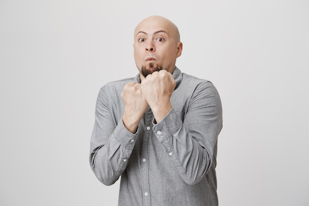 Hombre calvo peleando, levanta los puños cerrados en pose de boxeo