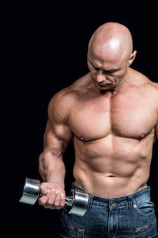 Hombre calvo que ejercita con pesas de gimnasia contra fondo negro