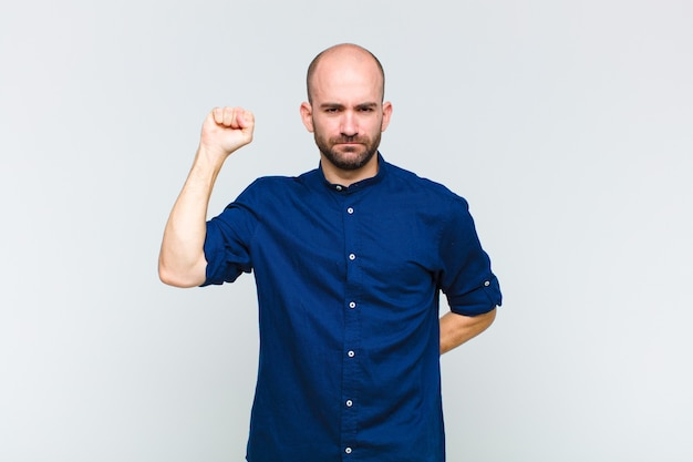 Hombre calvo que se siente serio, fuerte y rebelde, levanta el puño, protesta o lucha por la revolución