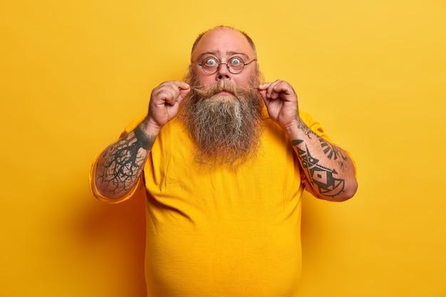 El hombre calvo sorprendido riza el bigote, tiene una barba espesa, mira con incredulidad, usa lentes transparentes, está vestido con ropa informal, tiene poses de vientre gordo en el interior. hombre gordo posa con expresión de asombro