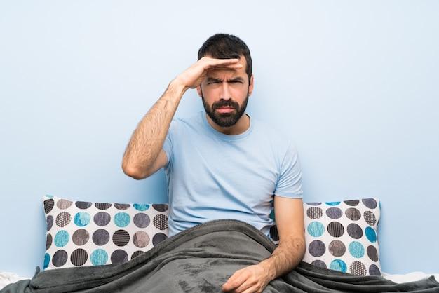 Hombre en la cama mirando lejos con la mano para mirar algo