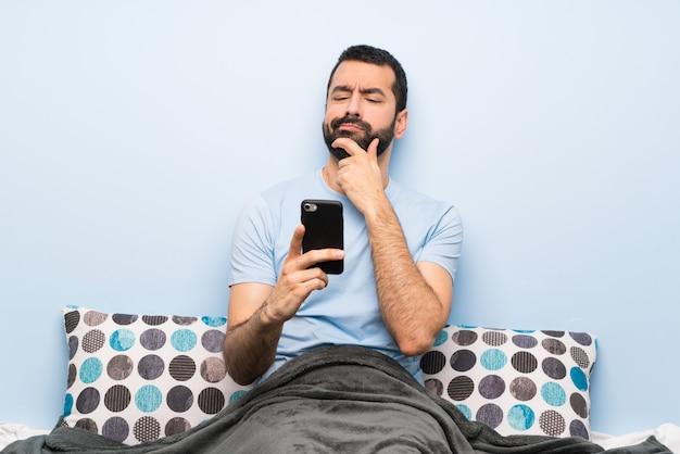 Hombre en la cama pensando y enviando un mensaje