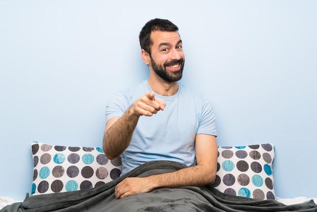 El hombre en la cama te señala con una expresión segura