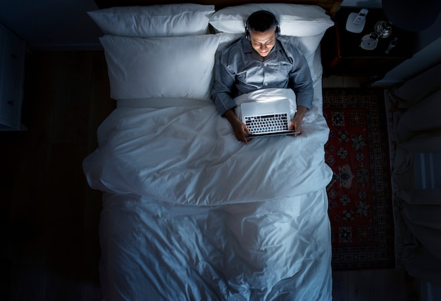Hombre en la cama usando su laptop y un auricular