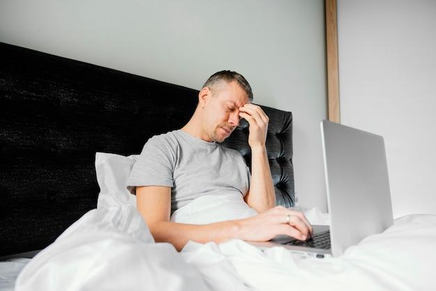Hombre, en cama, usar la computadora portátil