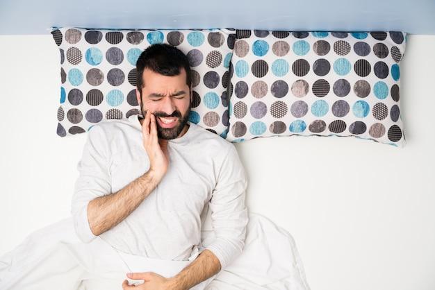 Hombre en la cama en la vista superior con dolor de muelas