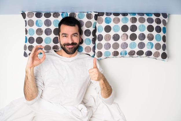 Hombre en la cama en la vista superior que muestra el signo ok y el pulgar arriba gesto