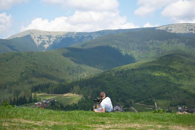 Hombre con cámara se encuentra en una colina y fotografía naturaleza. día de verano