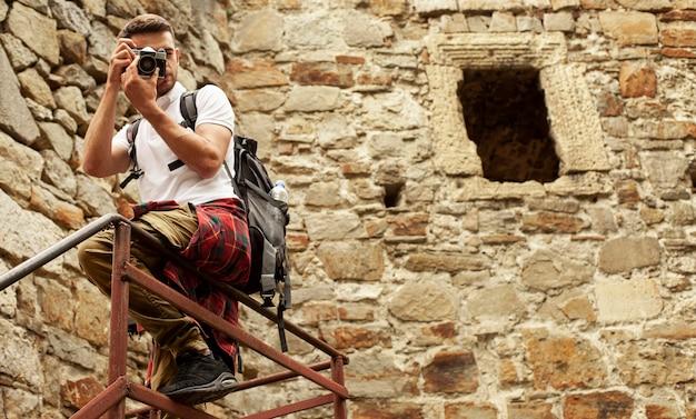Hombre con cámara en las escaleras del castillo tomando fotos