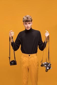 Hombre con una cámara en un escenario amarillo