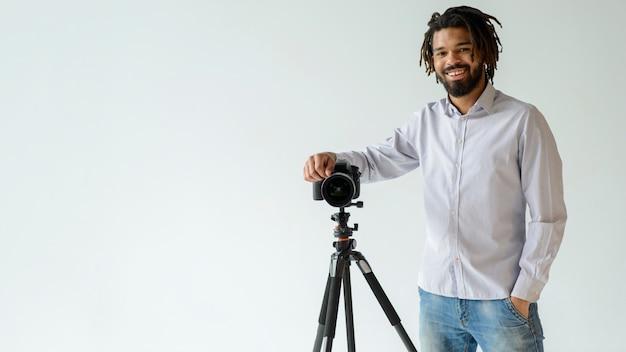 Hombre con cámara y fondo blanco.