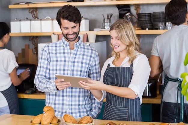 Hombre y camarera de pie en el mostrador con tableta digital