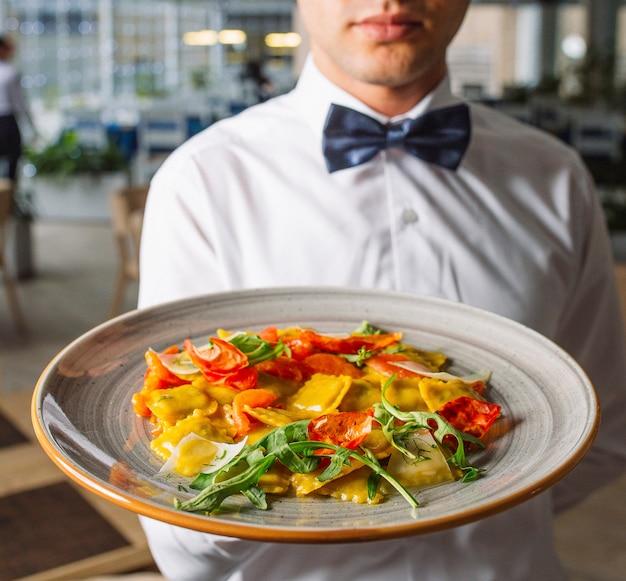 Hombre camarero sosteniendo un plato grande de ravioles con hojas de rúcula, queso parmesano
