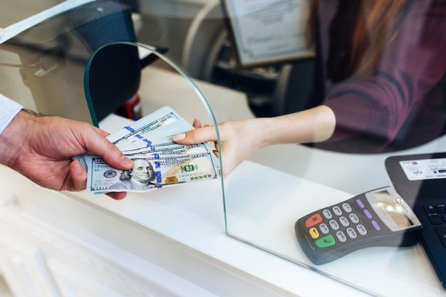 El hombre cambia el dinero en un cambio de divisas, una gran suma de dólares, un aumento en el tipo de cambio, cerca de un dinero que cambia de manos