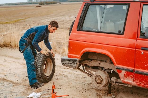 El hombre cambia la rueda manualmente en un camión todoterreno 4x4