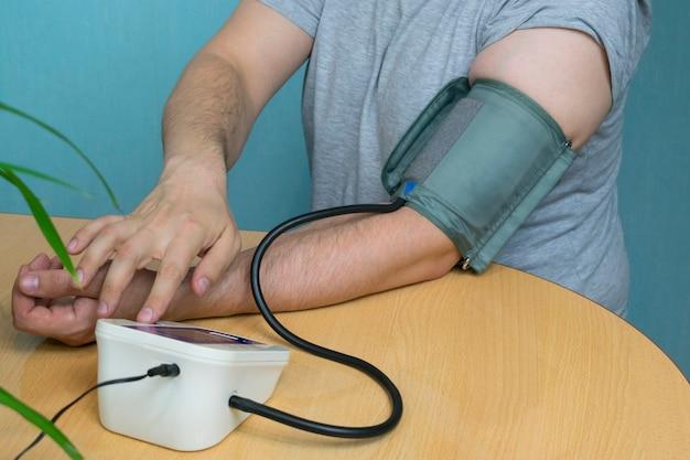 Un hombre cambia su presión con un tonómetro sentado en una mesa con un brazalete en la mano, en la mesa hay una planta de la casa cerca