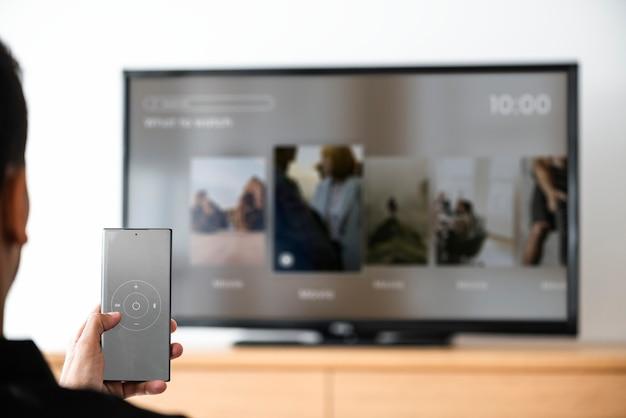 Hombre cambiando de canal de televisión por su teléfono inteligente