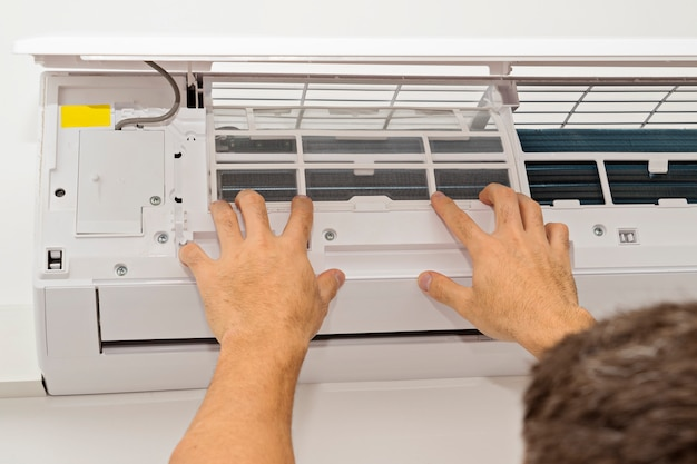 Hombre cambiando el filtro en el aire acondicionado