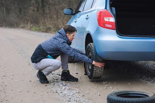 El hombre está cambiando el neumático con la rueda en el auto