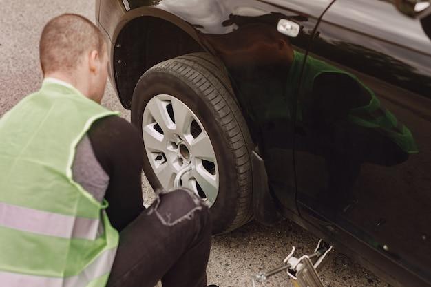 Hombre cambiando la rueda rota en coche
