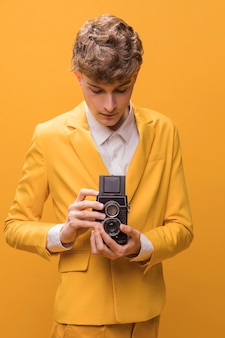 Hombre con un camcorder en un escenario amarillo