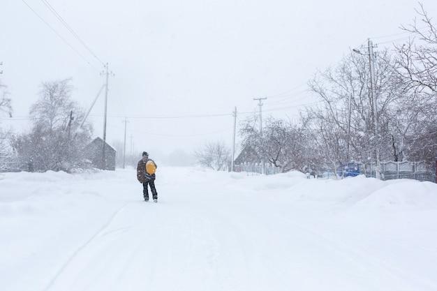 El hombre camina por la calle en invierno