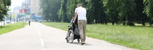 Hombre camina con mujer en silla de ruedas en el parque