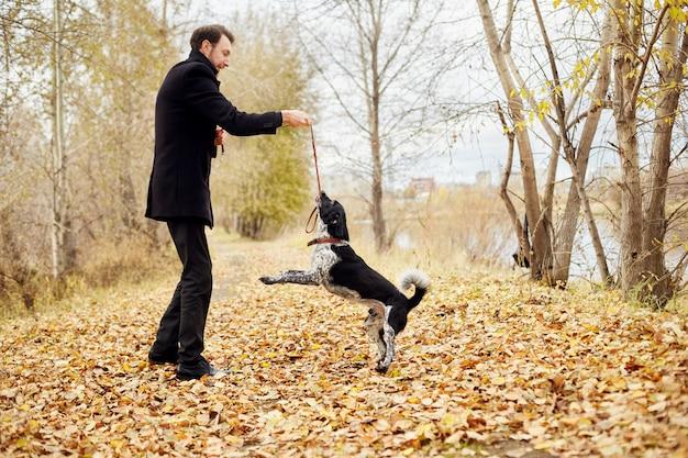 El hombre camina en el otoño con el perro spaniel parque de otoño