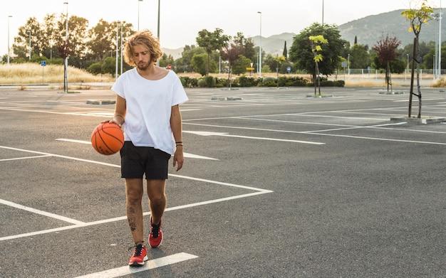 Hombre caminando con el baloncesto en la cancha