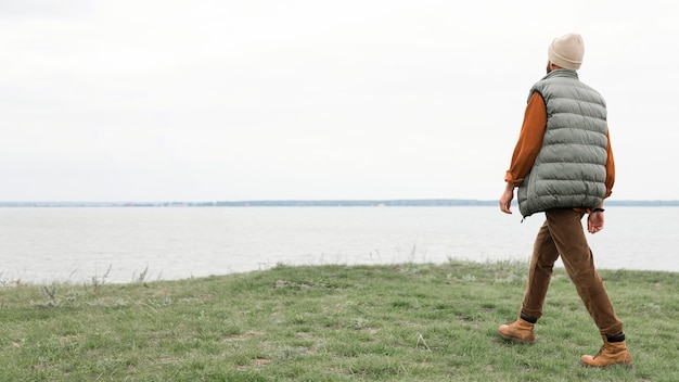 Hombre caminando por el campo hacia el agua