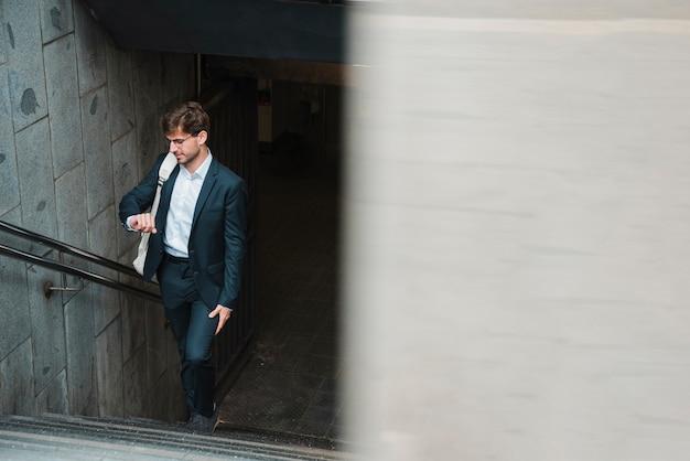 Hombre caminando en la escalera del metro mirando el tiempo