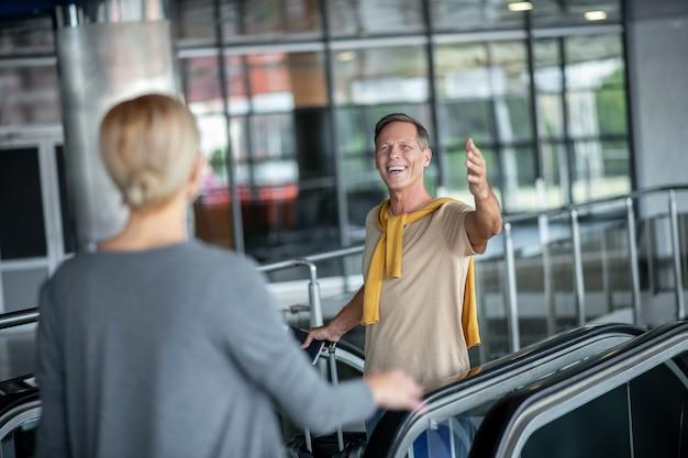 Hombre caminando por las escaleras mecánicas gesticulando en saludo