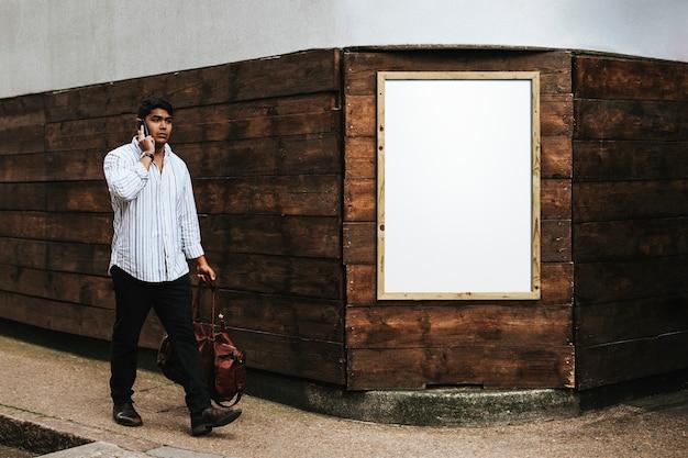 Hombre caminando por un marco de madera en blanco sobre una pared de ladrillos