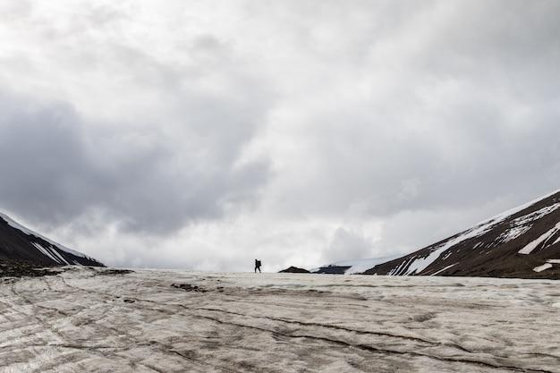 Hombre caminando hacia la naturaleza en un glaciar en svalbard