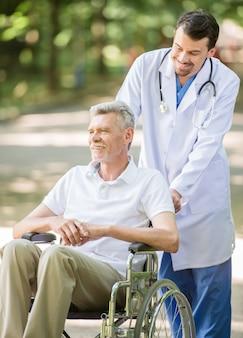 El hombre está caminando con el paciente mayor en silla de ruedas.