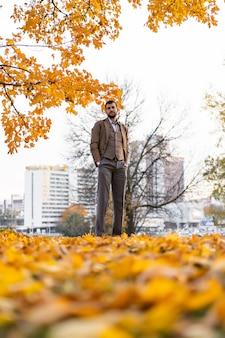 Hombre caminando en el parque otoño