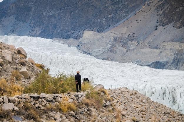 Un hombre caminando por la pista para ver el glaciar passu. pakistán.