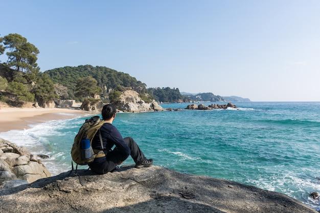 Hombre caminando entre las rocas cerca de una playa paradisíaca