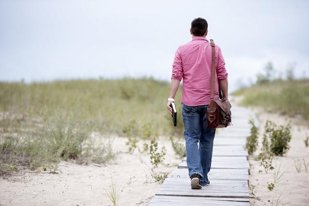 Hombre caminando sobre un camino de madera con su bolsa y sosteniendo la biblia