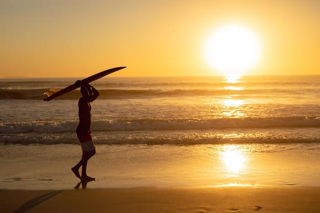 Hombre caminando con tabla de surf sobre su cabeza en la playa