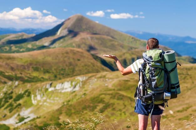 Hombre caminante de pie en la cima del pico rocoso con vistas al paisaje de montaña.