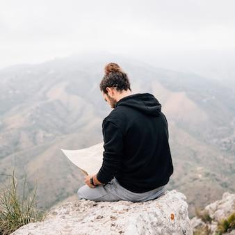 Hombre caminante sentado en la cima de la roca mirando el mapa