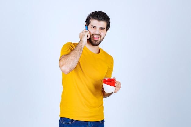 Hombre de camisa amarilla hablando por teléfono.