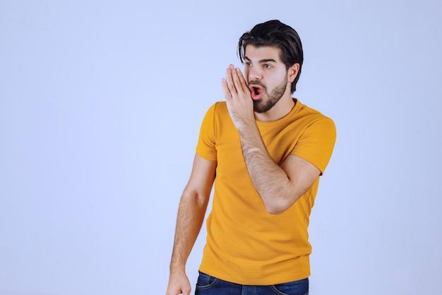 Hombre de camisa amarilla haciendo chismes.