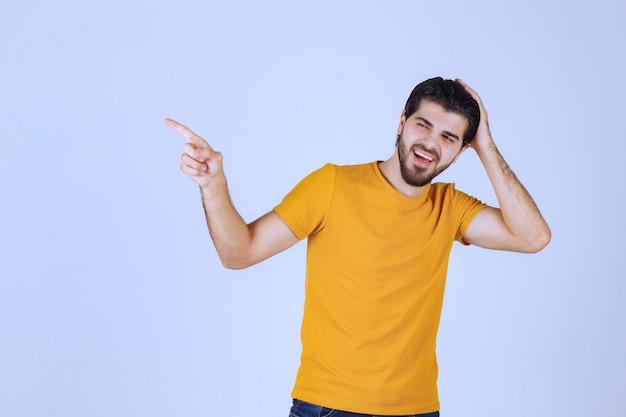 Hombre con camisa amarilla mostrando algo a la izquierda.